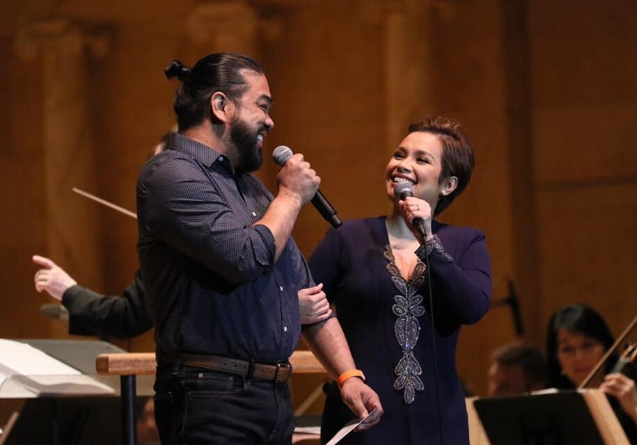 A man and a woman both holding a microphone singing to each other. They are both smiling.