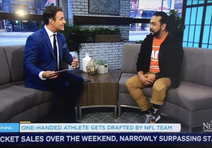 Ben Mulroney interviewing Aristotle on Your Morning TV show. There is a camera man on the foreground.